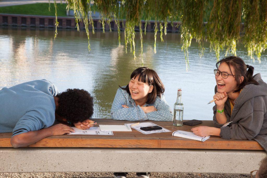 Drei junge Menschen sitzen an einem Tisch und lachen.