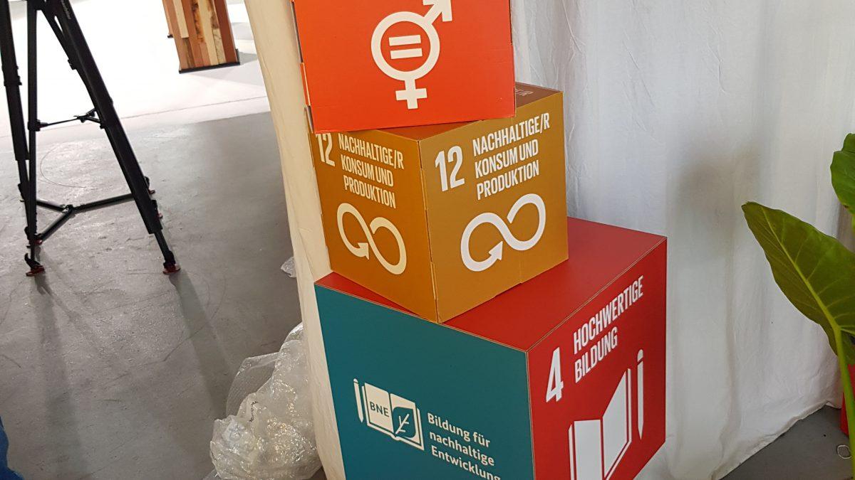 Gestapelte SDG-Würfel aus Pappe und Holz stehen hinter den Kulissen bei der youcoN.