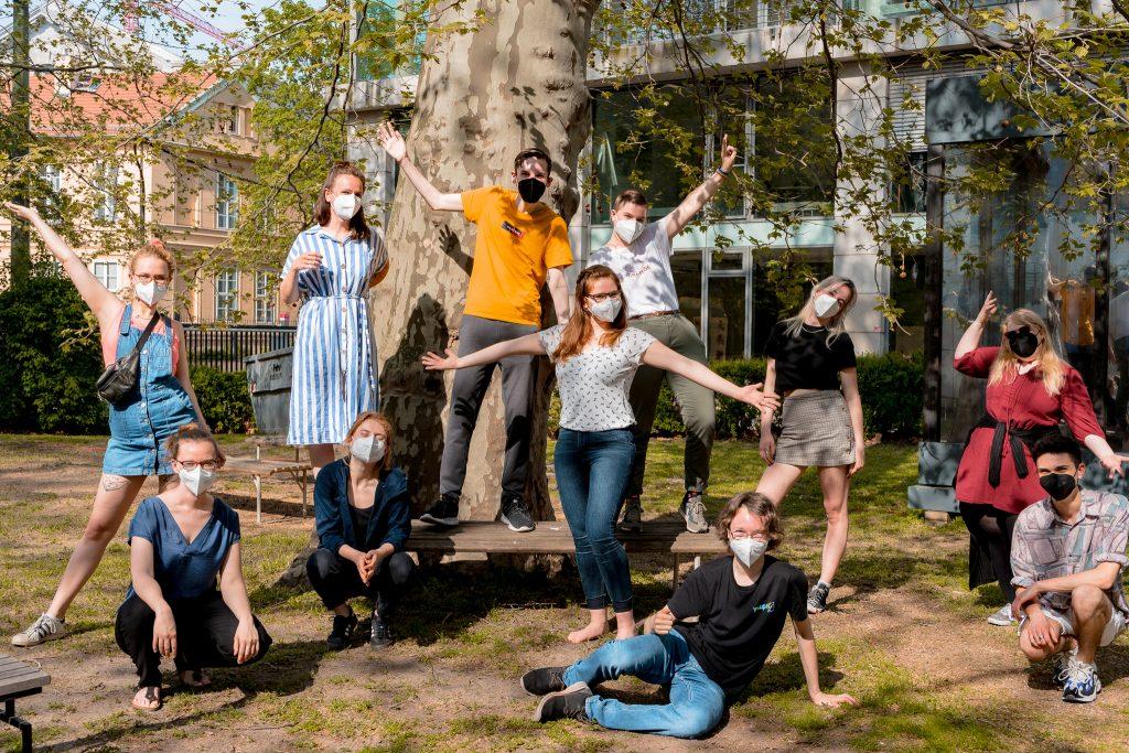 Eine Gruppe junger Menschen steht vor einem Baum und trägt Corona-Masken.